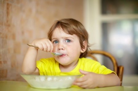 2 years child himself eats from plate  with spoon photo