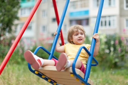 totter: Baby girl on swing against urban  landscape