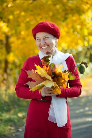 Portrait of  laughing mature woman  in autumn park photo