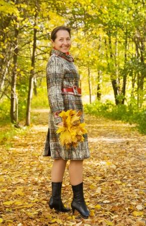 seasonable: senior woman  in coat standing outdoors in autumn
