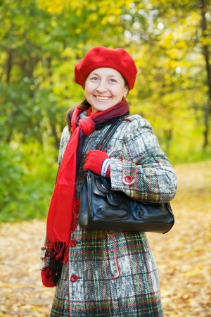 Happy mature woman  in coat walking outdoors in autumn