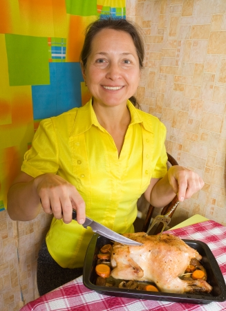 Mature woman with cooked baked chicken on roasting pan in kitchen Stock Photo - 14471428