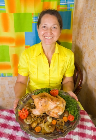 Mature woman with cooked baked chicken on tray in kitchen photo