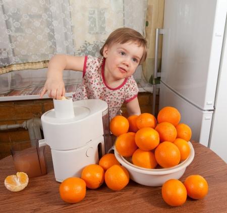 Baby girl adding orange to juicer in home kitchen photo