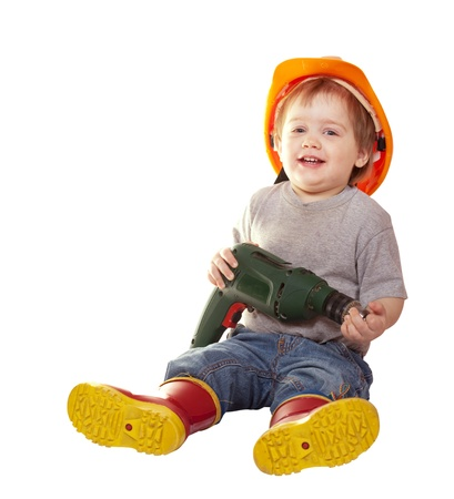 Toddler in hardhat with drill. Isolated over white background photo