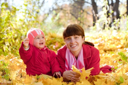 Mother and   baby laying on maple leaves in autumn park Stock Photo - 14509992