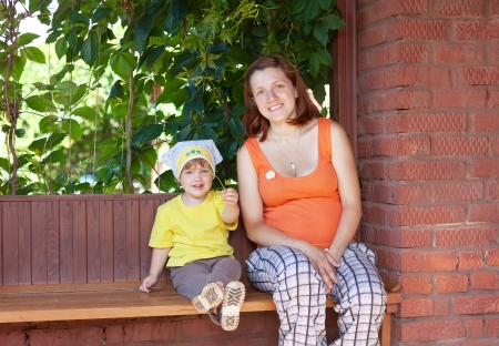 Happy mother and child sits on bench in veranda Stock Photo - 14517160