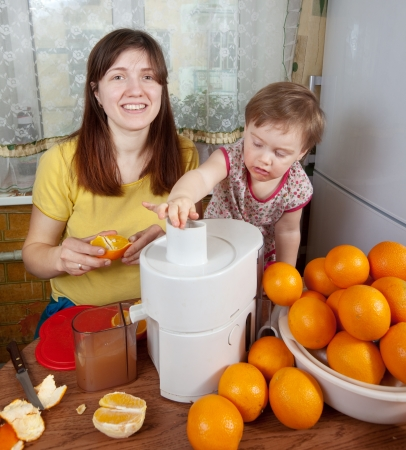 mother and daughter making fresh orange juice in home kitchen  photo