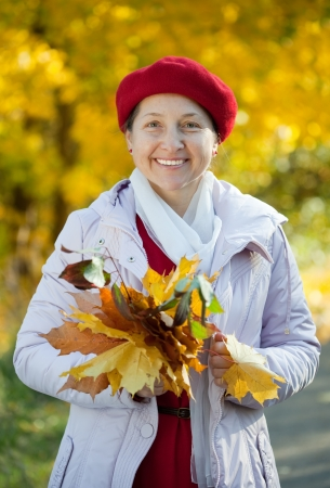 happy mature woman  in autumn park photo
