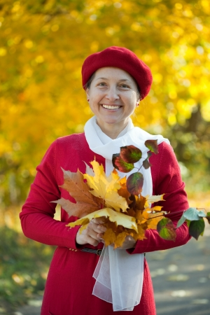 Portrait of mature woman  in autumn park  photo
