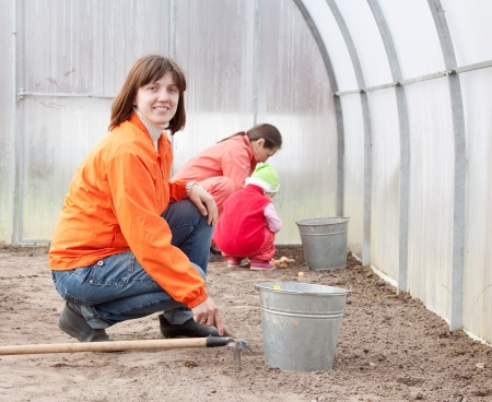 Happy family works in greenhouse photo