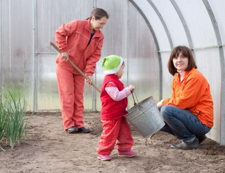Les femmes heureuses avec des ?uvres de l'enfant à serre au printemps Banque d'images - 14530861