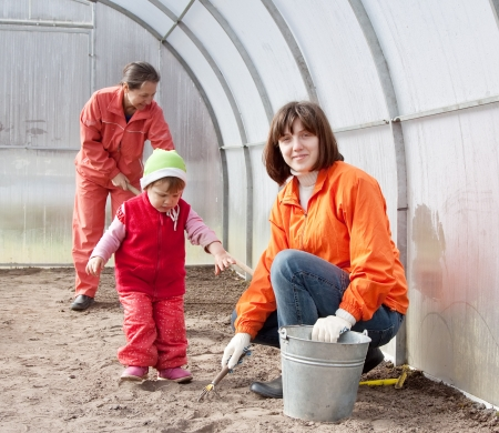 Happy family sows seeds in soil at hothouse photo
