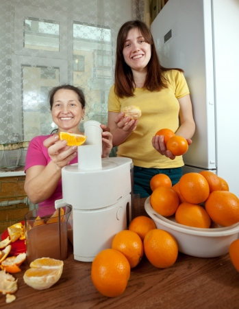 Two women  making fresh orange juice in home kitchen  photo