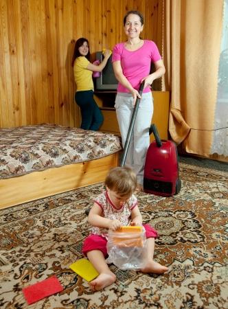 La famille nettoie dans le salon avec un aspirateur Banque d'images - 14530909