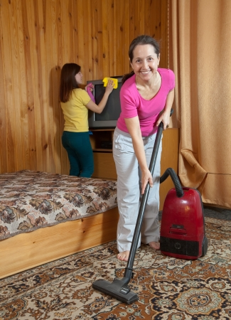 Women are cleans with vacuum cleaner in home photo