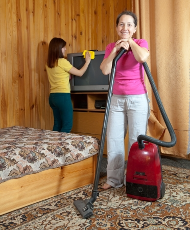 vacuuming: Women cleaning with vacuum cleaner in living room