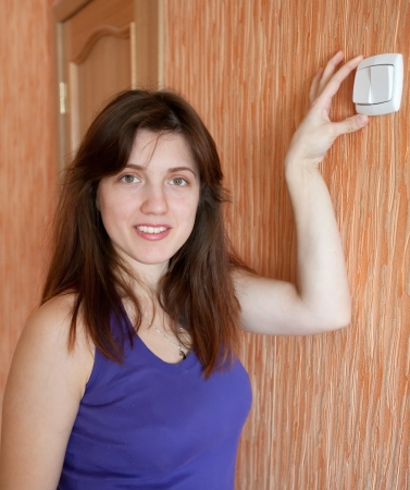 Young woman with light switch in home Stock Photo - 14531008