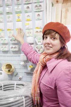 Young woman chooses  switch in  electrical store Stock Photo - 14530998