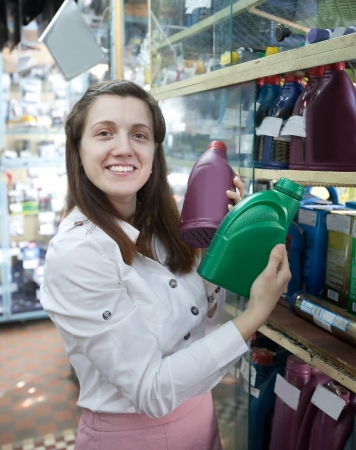 motor oil:   woman chooses  motor oil in  auto spare parts store Stock Photo