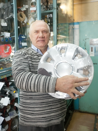 mature man buys  automotive wheel cover in  auto parts store Stock Photo - 14531019