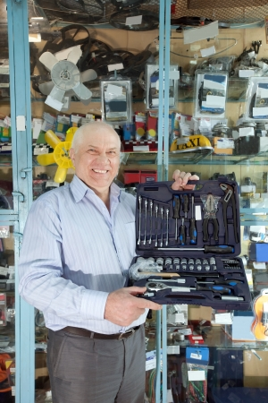 mature man holds  automotive  correction tool set in  auto parts store photo