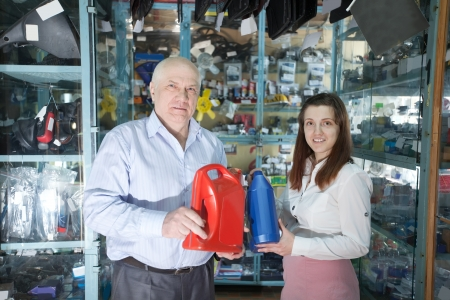 motor oil: man and woman with canister of motor oil in auto store Stock Photo
