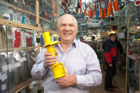 shock absorber: mature man holds  shock absorber  in  auto parts store Stock Photo