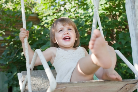 Laughing girl on swing in summer park photo