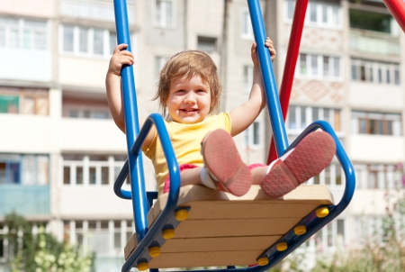 Baby girl on swing against urban  landscape photo