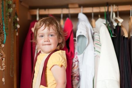 baby wardrobe:  Baby girl  chooses dress in parents wardrobe  Stock Photo