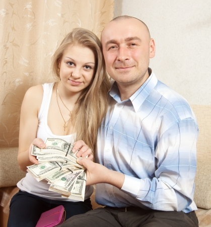 Happy young family with many US dollars  in home photo
