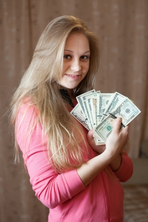 Happy young woman with bundles of US dollars  in home