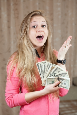 Happy young woman shows bundles of US dollars  in home Stock Photo - 14595111