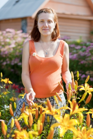gravida: pregnant woman in yard with Lilium plant