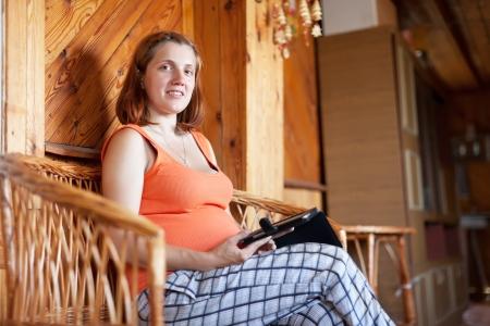 pregnant woman reads e-book in home interior Stock Photo - 14594559