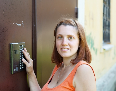 Young woman uses intercom in steel door photo