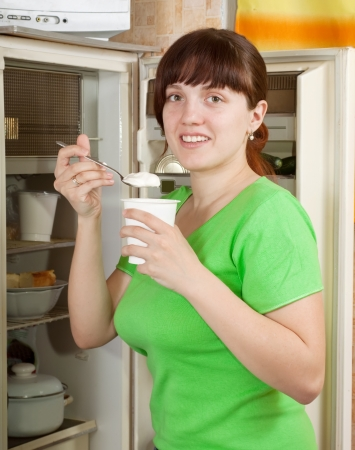 whig: Young woman near opening fridge eating yoghurt Stock Photo