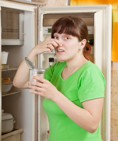 young woman holding her nose because of bad smell from food near refrigerator  at home Stock Photo - 14596688