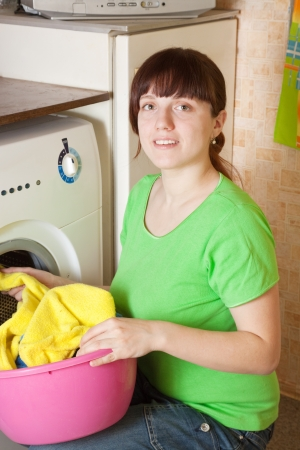 Young woman doing laundry at her home photo