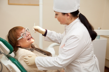 Mature patient and  dentist during dental medical treatment photo