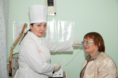Female patient and doctor during  physiotherapy of ear photo