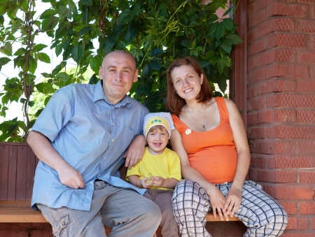 Happy family of three sits on bench in veranda photo