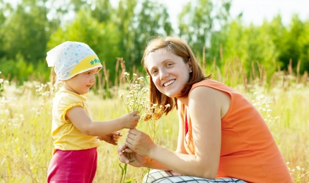Happy mother with daughter in summer daisy plant photo
