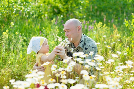 Happy father with child sits in camomile plant photo