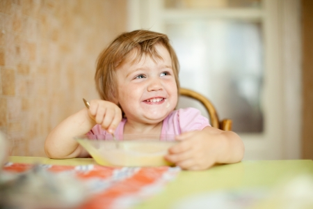 1 2 month: child eats with spoon in home Stock Photo