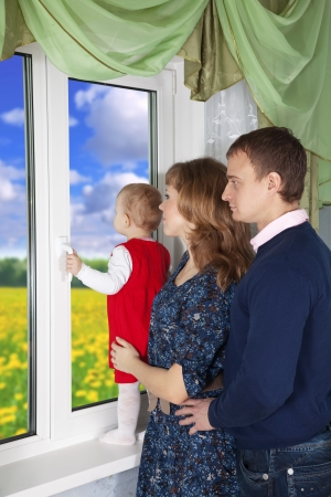 Family looking out the window in home photo