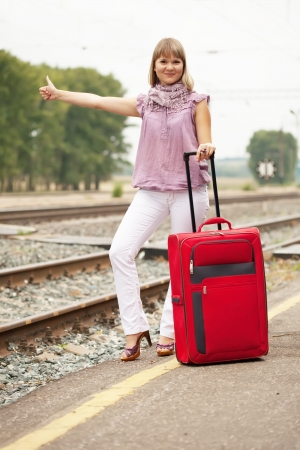woman with luggage waiting  train on  railroad photo