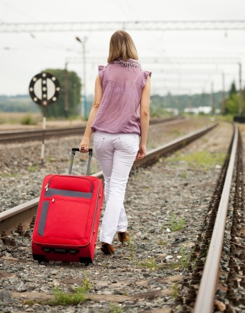 Rear view of woman with luggage walking on rail road photo