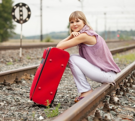 woman with luggage sitting on rail photo